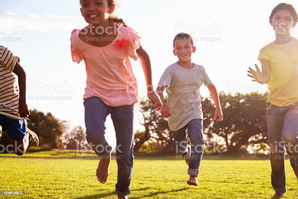 Drei glückliche Kinder, die in einem Feld im Sommer barfuß laufen – Foto