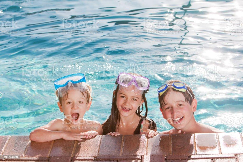 Three Happy Children Swimming in Pool royalty-free stock photo