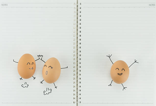 Three happy eggs with copy space on blank notebook paper stock photo
