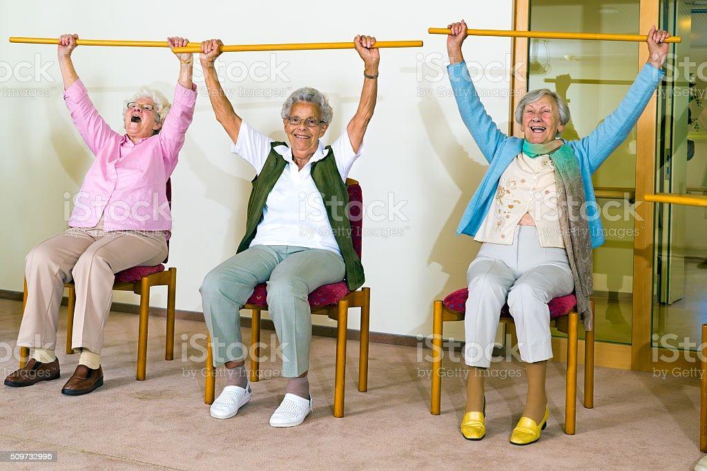 Three happy elderly ladies doing exercises. stock photo