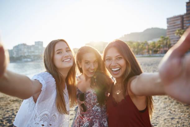 Three happy female friends taking selfie on beach stock photo