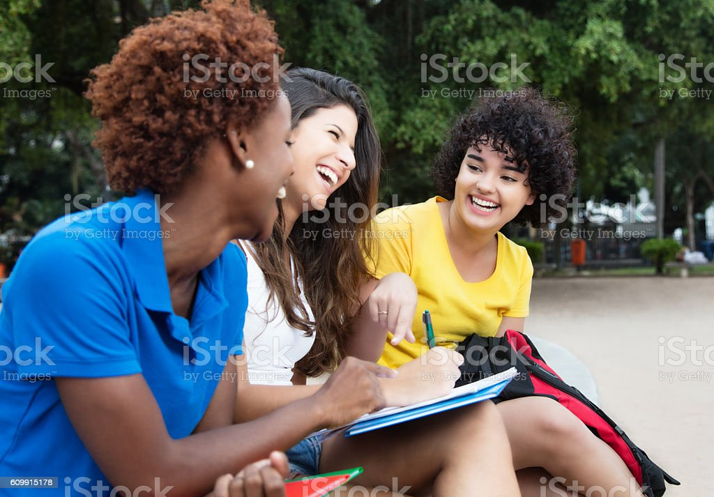 Three happy female students learning outdoor stock photo