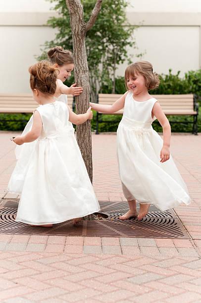 drei glückliche blume mädchen spielen in eleganter kleider - hochzeitsfeier mit kindern stock-fotos und bilder