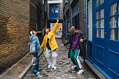istock Three happy friends dancing together in the city 1213297859