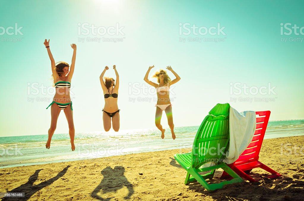 Drei glückliche Freunde springen am Strand für den Sommer Lizenzfreies stock-foto