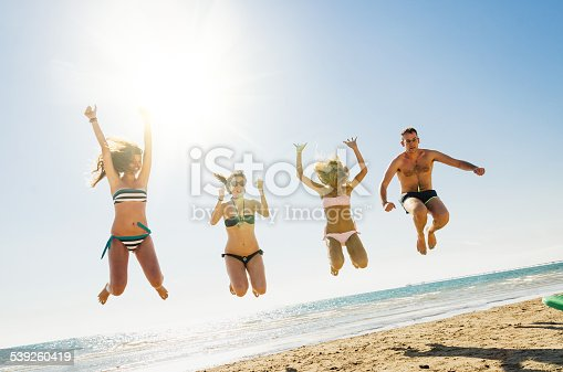 Three happy friends jumping on the beach for summer