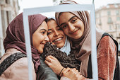 Three happy friends smiling to camera taking a selfie.