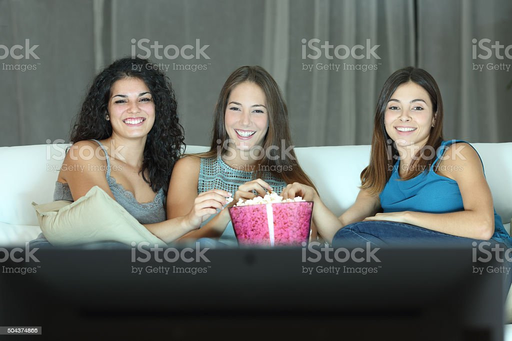 Three happy friends watching tv stock photo