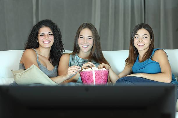 drei glückliche freunde vor dem fernseher - mädchen night snacks stock-fotos und bilder