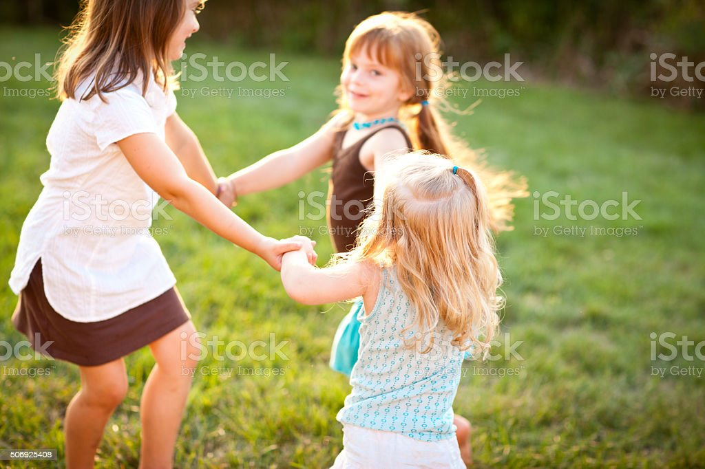 Trois heureux jeunes filles tenant les mains en vélo à l'extérieur - Photo