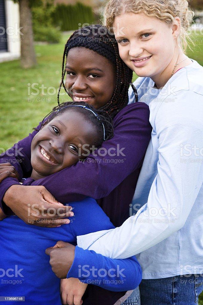 Three Happy Girls Hugging Outside royalty-free stock photo