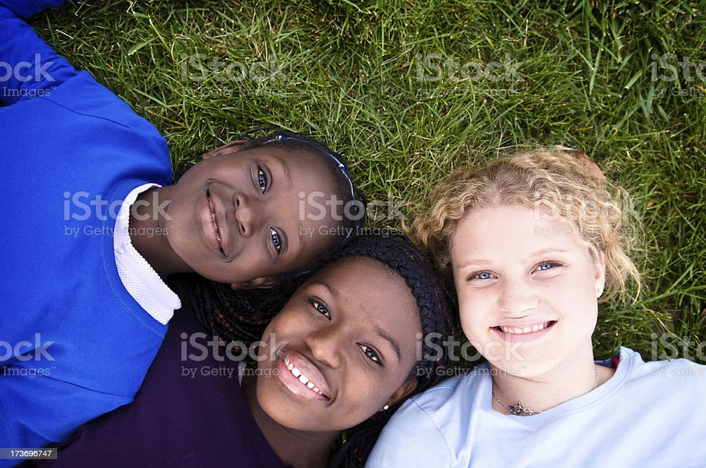 Three Happy Girls Lying in the Grass royalty-free stock photo