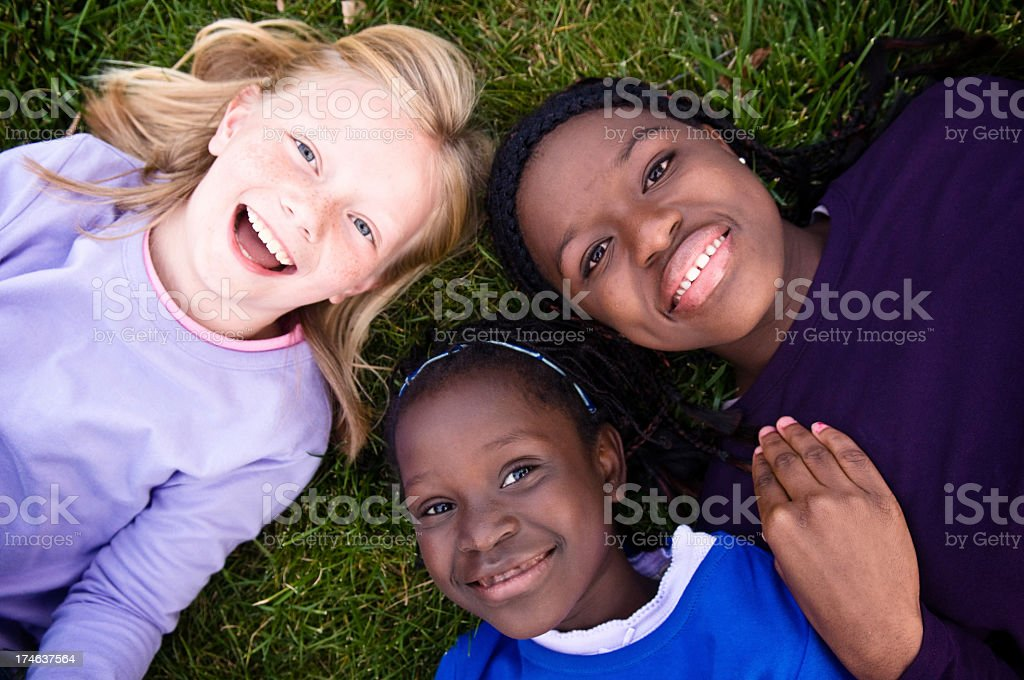 Three Happy Girls Smiling and Lying in the Grass royalty-free stock photo