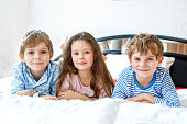Three happy kids in pajamas celebrating pajama party. Preschool and school boys and girl having fun together. Children playing together in bed. Making pillow fight.