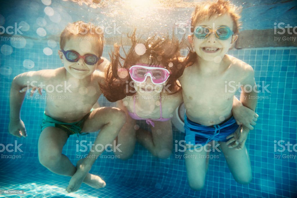 Three happy kids playing underwater stock photo