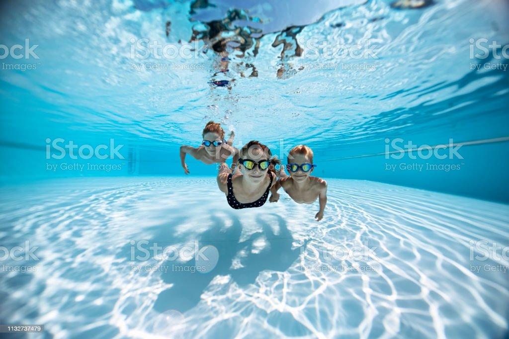 Drei glückliche Kinder schwimmen unter Wasser im Pool – Foto