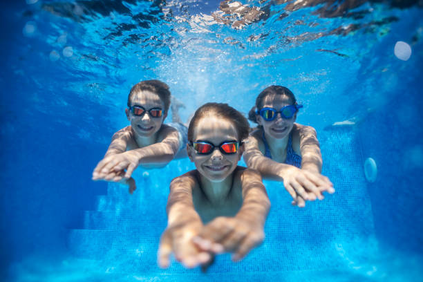 Three happy kids swimming underwater in pool Three smiling kids enjoying underwater swim in the pool. Nikon D850 swimming goggles stock pictures, royalty-free photos & images