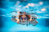 Three smiling kids enjoying underwater swim in the pool.\nNikon D810