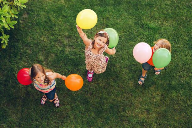 Drei fröhliche kleine Kinder, die mit bunten Luftballons im Freien spielen, oben – Foto