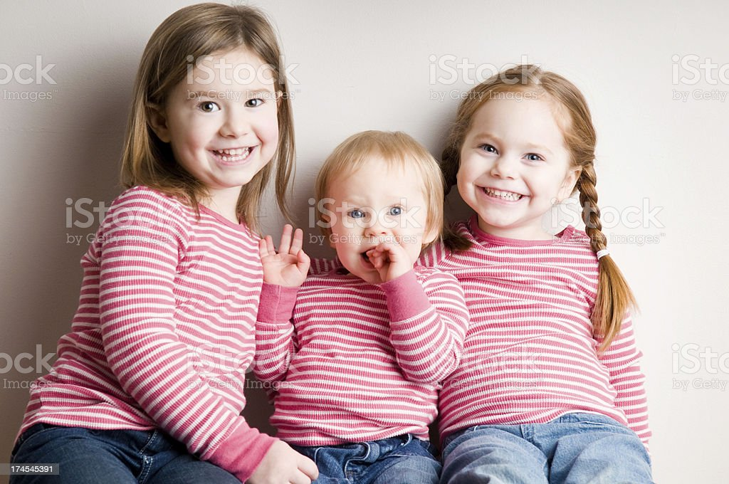 Three Happy, Matching Sisters Sitting Together and Smiling stock photo