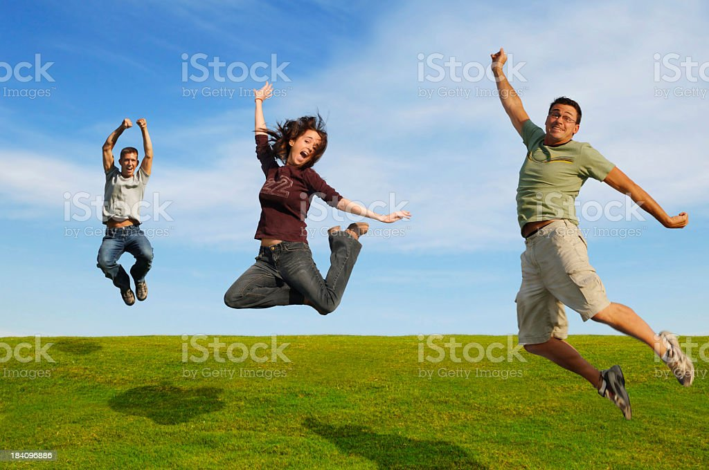 Three happy people jumping in a field royalty-free stock photo
