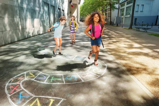 drei glückliche schulpflichtige kinder spielen, himmel und hölle - himmel und hölle spiel stock-fotos und bilder