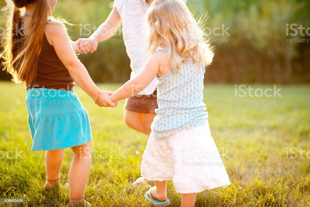 Trois soeurs heureuse tenant les mains dans un cercle extérieur - Photo