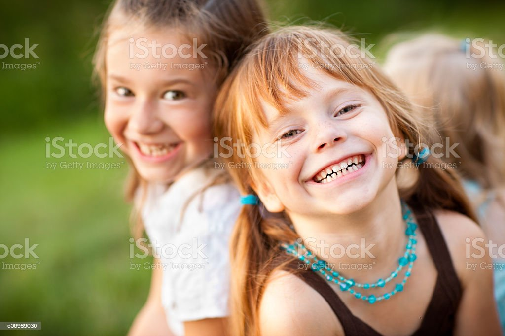 Three Happy Sisters Laughing While Sitting Together Outside Color stock photo of three happy little girls who are sisters sitting and laughing together outside. 2-3 Years Stock Photo