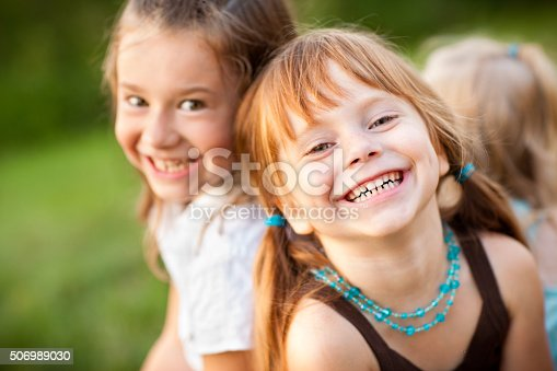 istock Three Happy Sisters Laughing While Sitting Together Outside 506989030