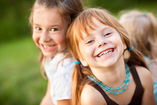 Three Happy Sisters Laughing While Sitting Together Outside Stock Photo - Download Image Now