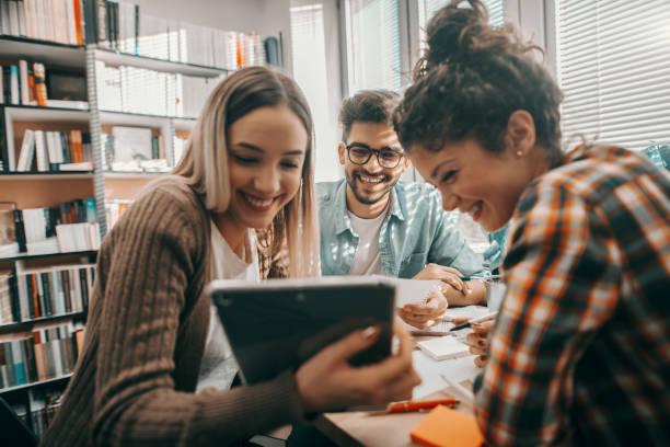 drei glückliche schüler kleideten sich lässig mit tablet für schulprojekt und saßen am schreibtisch in der bibliothek. - jugendalter stock-fotos und bilder