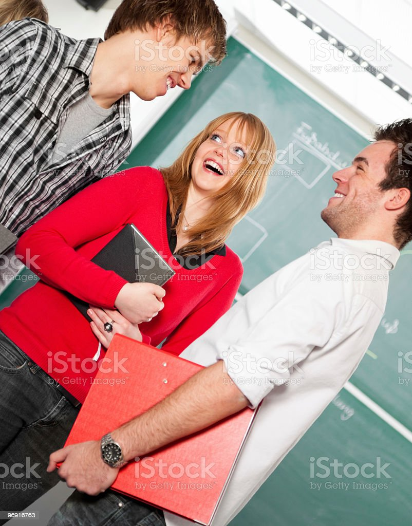 Three happy students in class or university royalty-free stock photo
