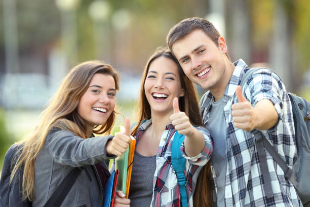 three happy students with thumbs up - student stock photos and pictures