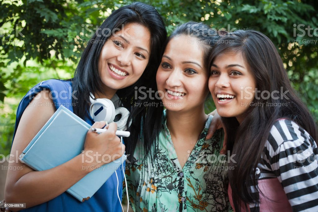 Three happy teenage girl students from different ethnicity in nature. stock photo