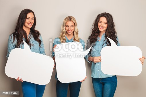 istock three happy women in jeans clothes holding speech bubbles 598962446
