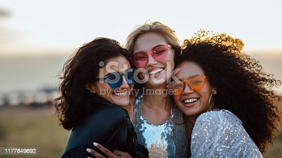 Three happy women wearing sunglasses hugging at evening outdoors