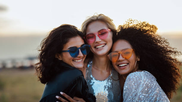 Three happy women wearing sunglasses hugging at evening outdoors stock photo