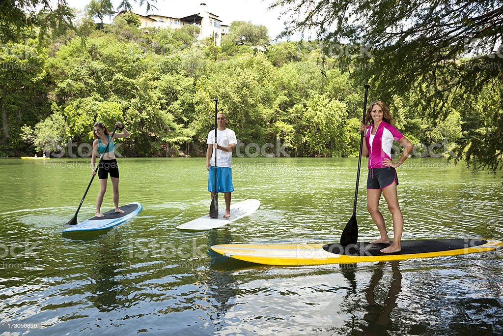 Three happy young adults on paddleboards in Colorado River. royalty-free stock photo