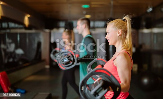 610237160istockphoto Three happy young athletes lifting weights in a group training. 975196506