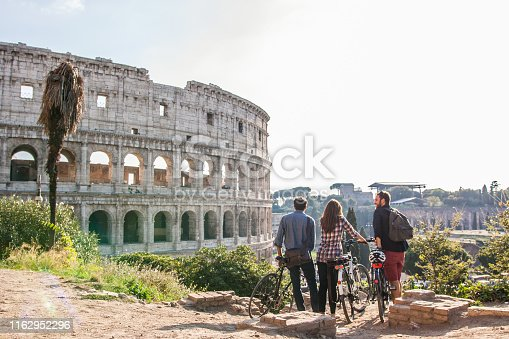 Three happy young friends tourists with bikes at Colosseum in Rome having fun