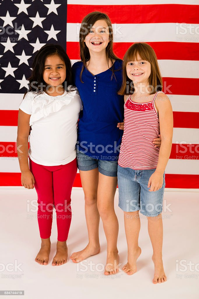 Three Happy Young Girls Standing in Front of American Flag stok fotoğrafı