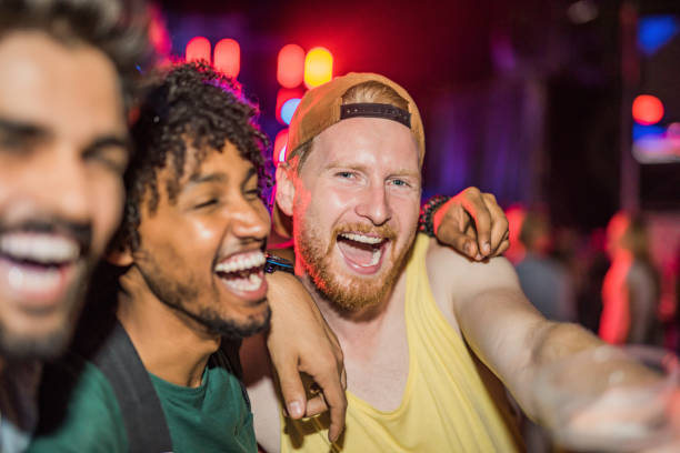 three happy young men partying at music festival at night. - concert selfie stock photos and pictures