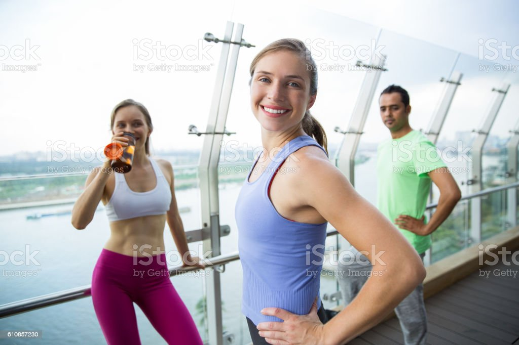 Three happy young people relaxing after training stock photo