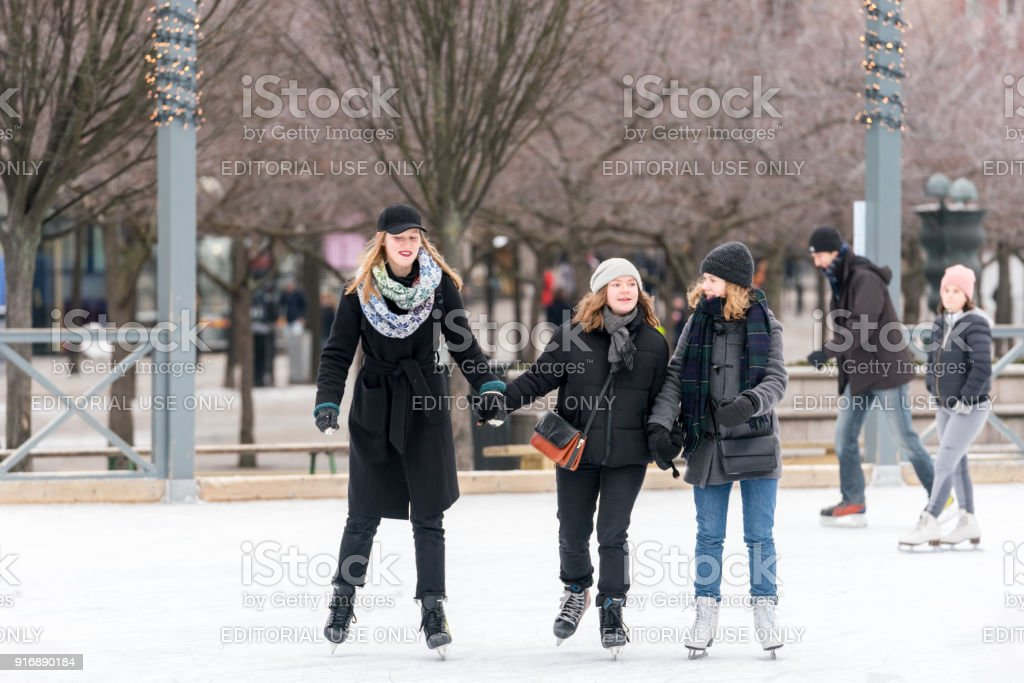 Three happy young woman skating at a public ice skating rink outdoors in the city. stock photo