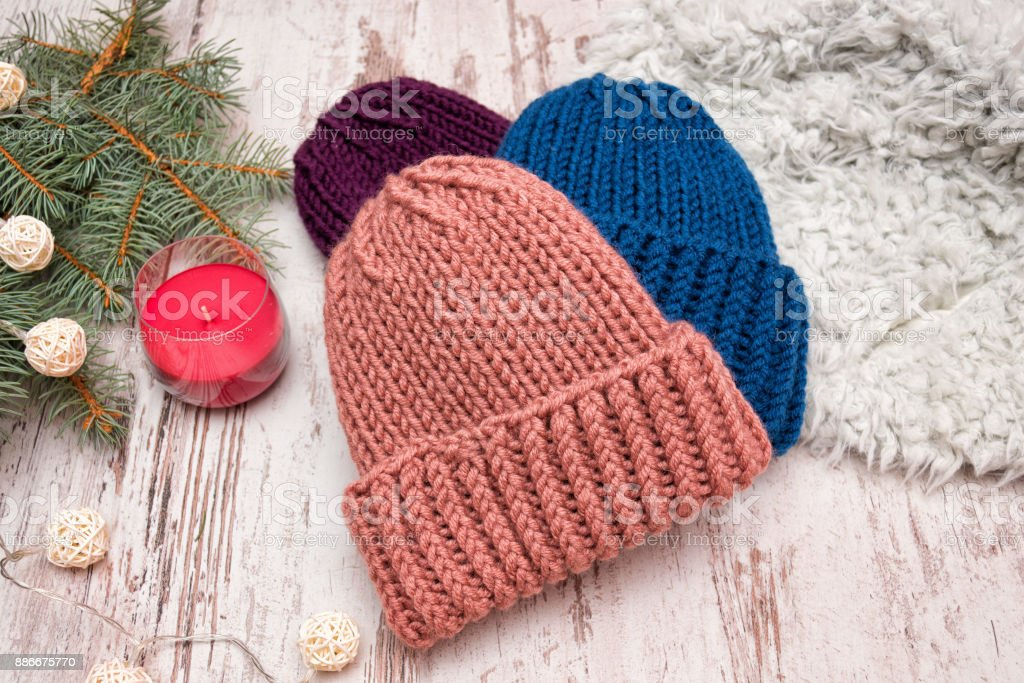 Three hats. Blue, coral and purple. Spruce branch, garland and candle. Wooden background. New Year's concept. stock photo