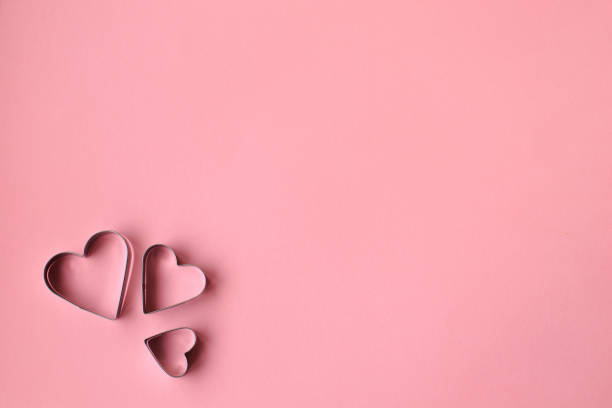 Three heart shaped cookie cutters over a pink background. Valentine's Day. Three heart shaped cookie cutters over a purple background. Valentine's Day. Love concept. cookie cutter stock pictures, royalty-free photos & images