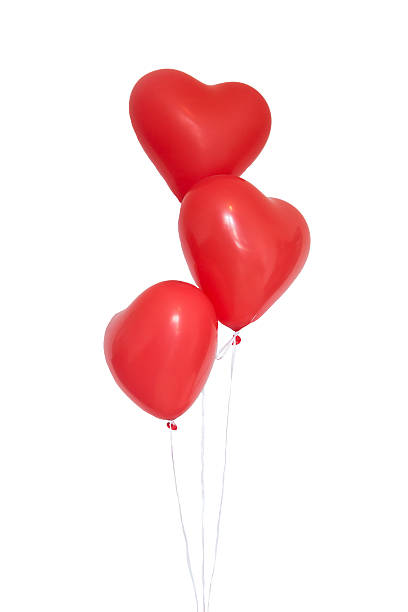 Three heart shaped red balloons on white background stock photo