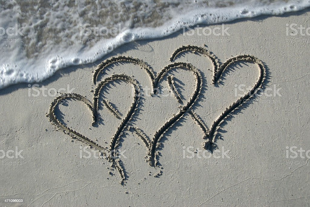 Three Hearts in the Sand with Wave stock photo