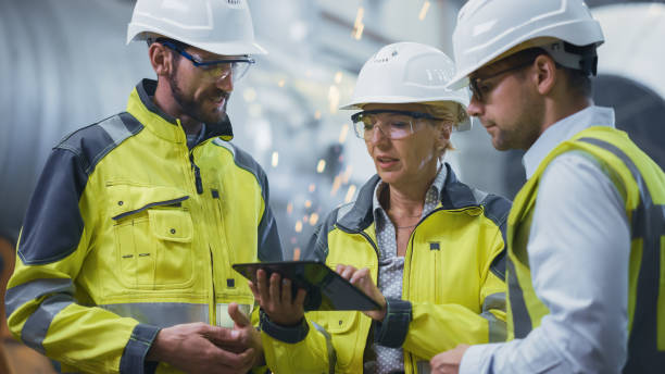 Three Heavy Industry Engineers Stand in Pipe Manufacturing Factory, Use Digital Tablet Computer, Have Discussion. Large Pipe Assembled. Design and Construction of Oil, Gas and Fuels Transport Pipeline stock photo