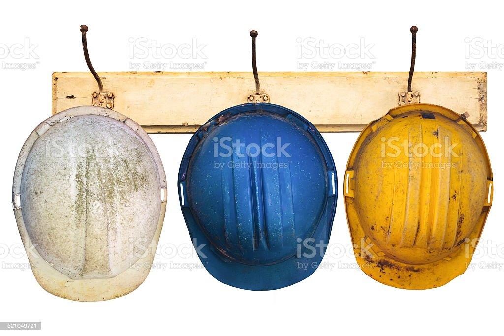Three helmets hanging on a hat-rack stock photo